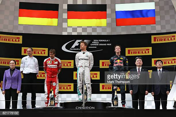 The top three Nico Rosberg of Germany and Mercedes GP Sebastian Vettel of Germany and Ferrari and Daniil Kvyat of Russia and Red Bull Racing on the...