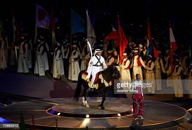 The torchbear emerges on horseback to light the flame inside the stadium during the Opening Ceremony of the 15th Asian Games Doha 2006 at the Khalifa...
