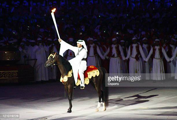 The torchbear makes his way to light the flame during the Opening Ceremony of the 15th Asian Games Doha 2006 at the Khalifa stadium in Doha Qatar on...