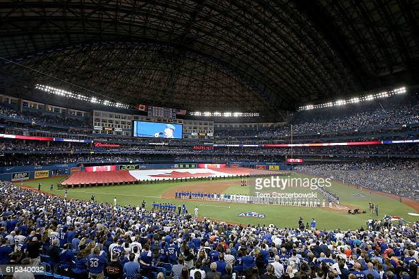 The Toronto Blue Jays and the Cleveland Indians stand for the national anthem prior to game three of the American League Championship Series at...