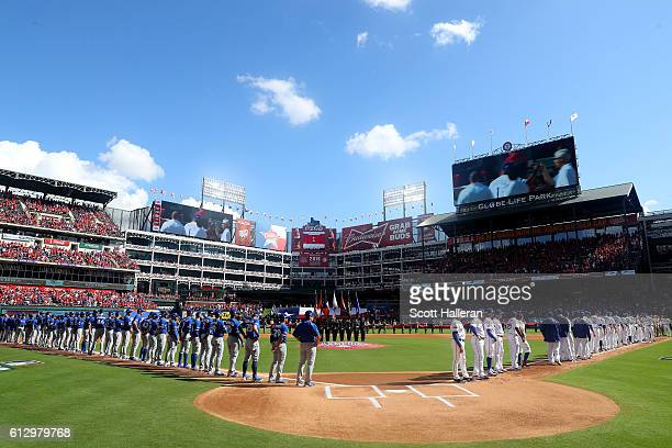 The Toronto Blue Jays and the Texas Rangers line up during the national anthem prior to game one of the American League Divison Series at Globe Life...