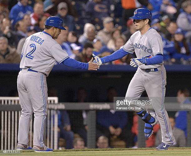 The Toronto Blue Jays' Colby Rasmus is congratulated by third base coach Luis Rivera after he hit a solo home run in the sixth inning against the...