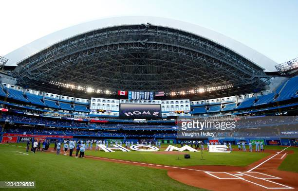 The Toronto Blue Jays line up behind a 'Home' sign to commemorate their first home game in Toronto this season prior to a MLB game against the Kansas...