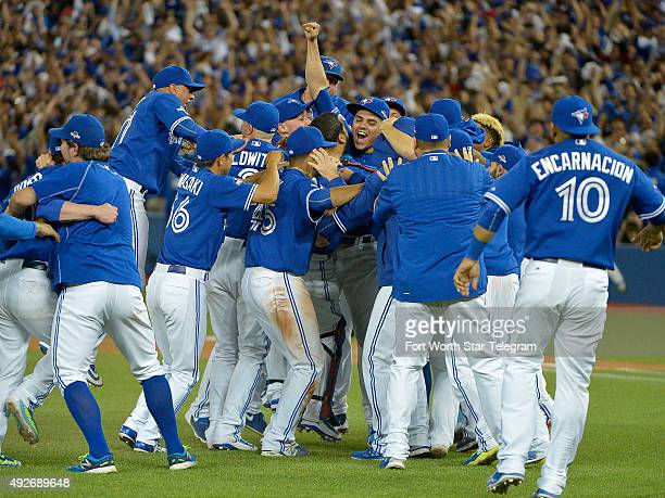 The Toronto Blue Jays mob relief pitcher Roberto Osuna after striking out the Texas Rangers' Will Venable for the last out of the game in Game 5 of...