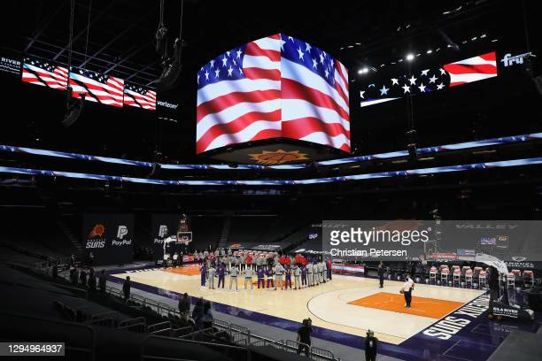 The Toronto Raptors and the Phoenix Suns stand arm-in-arm during the national anthem before the NBA game at Phoenix Suns Arena on January 06, 2021 in...