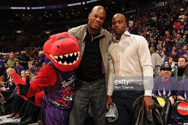 The Toronto Raptors mascot and former Toronto Raptors Antonio Davis and Alvin Williams watch during the game between the Toronto Raptors and the...
