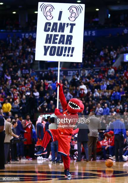 The Toronto Raptors mascot The Raptor waves a sign during the second half of an NBA game against the Miami Heat at Air Canada Centre on January 9...