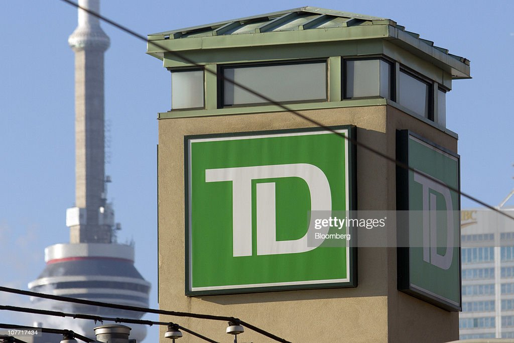 The Toronto-Dominion Bank (TD) logo is displayed on a newly-opened branch near the CN Tower, back left, in Toronto, Ontario, Canada, on Tuesday, Dec. 21, 2010. Toronto-Dominion Bank agreed to buy Chrysler Financial Corp. from Cerberus Capital Management LP for $6.3 billion in cash, adding an auto-finance company in its second-largest acquisition. Photographer: Norm Betts/Bloomberg via Getty Images