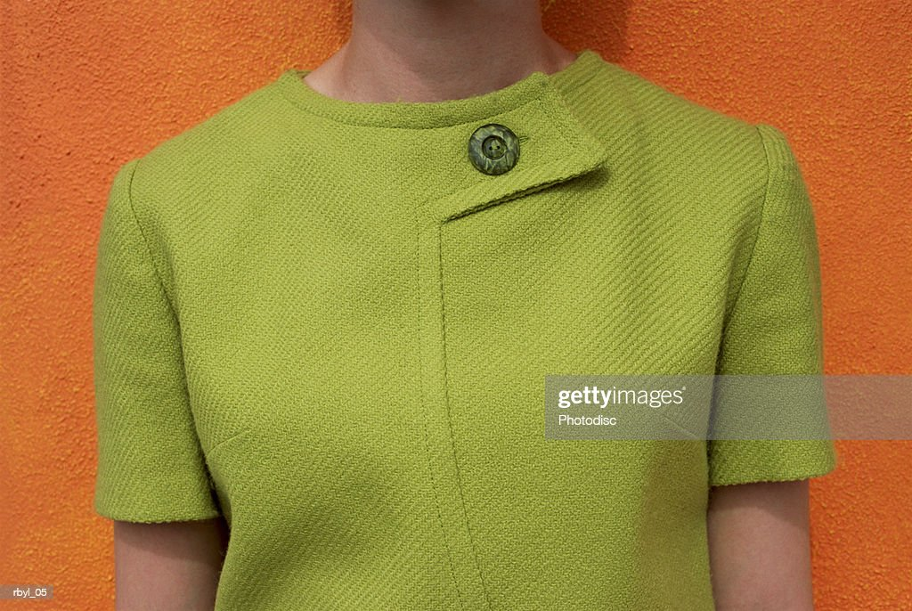 the torso areea of a young woman in a green dress against an orange wall : Foto de stock
