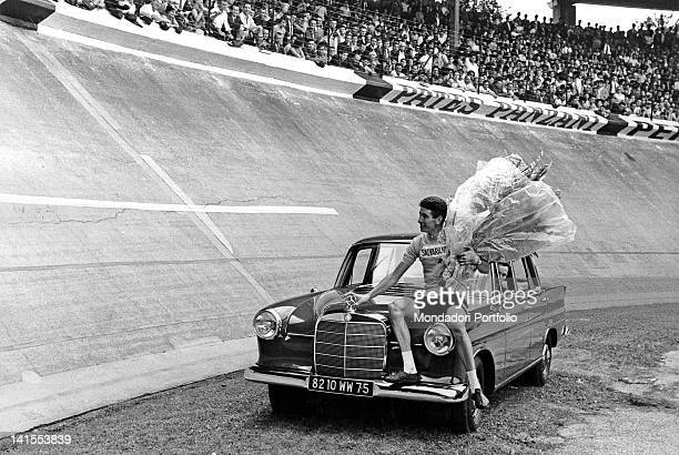The Tour de France winner Felice Gimondi sitting on the bonnet of the Mercedes that he has just won at Parc des Princes Paris 14th July 1965
