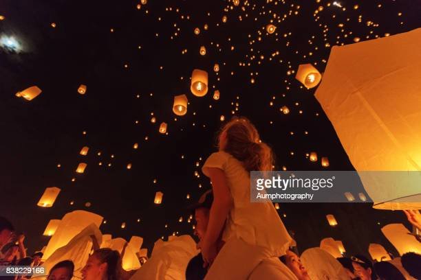 the tourist girl sit on father's neck looking the lanterns were floating in the sky. - yi peng stock pictures, royalty-free photos & images