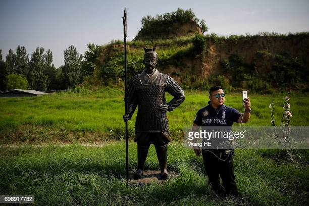 The Tourist uses iPhone take pictures with Ancient soldier statues at Hangu pass on June2017 in LuoyangHenan province£¬chinaHangu pass is one of the...