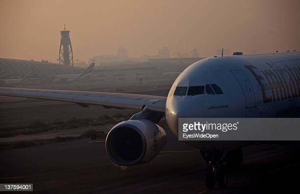The tower at Dubai Airport with a Airbus A330200 in the foreground before departure on December 25 2011 in Dubai United Arab Emirates
