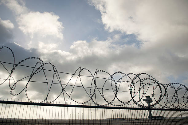 The tower is seen behind barbed wire at the new Berlin-Brandenburg ...
