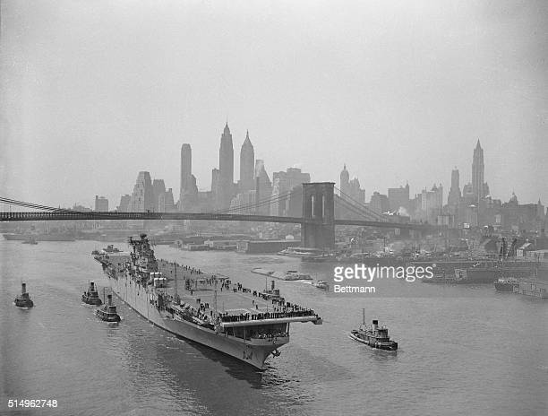 The towering skyscrapers of lower New York framed by Brooklyn Bridge in the backgrounds the aircraft carrier Leyte is shown sailing up the East River...