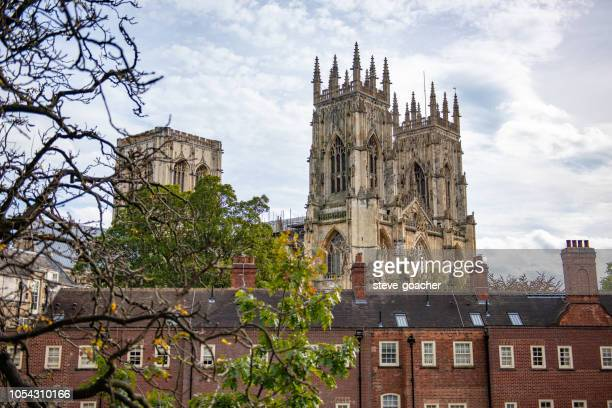 the towers of york minster beyond a row of terraced residential houses in the city. - york minster stock photos and pictures