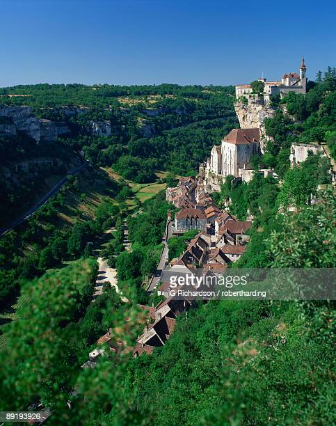 the town and church overlook a green valley at rocamadour, lot, midi pyrenees, france, europe - rocamadour stock pictures, royalty-free photos & images