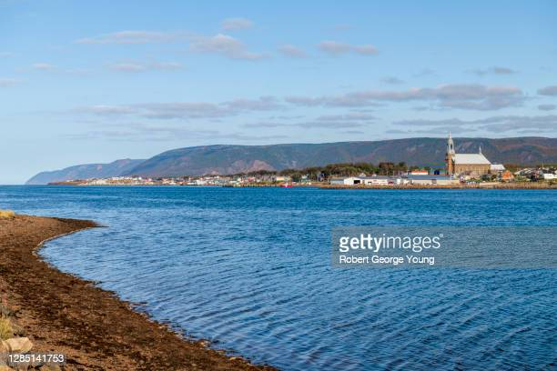 the town of chéticamp below the highlands of cape breton island. - cape breton island stock pictures, royalty-free photos & images