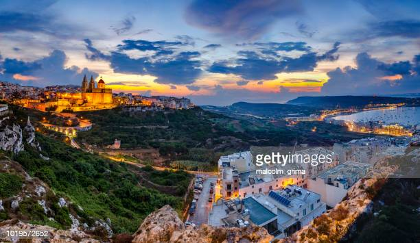 the town of mellieha sparkles at blue hour - maltese islands stock photos and pictures