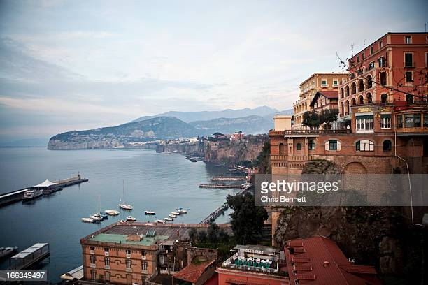 the town of sorrento, italy hugs the rugged cliffs overlooking the bay of naples. - sorrento stock pictures, royalty-free photos & images