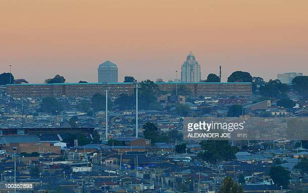 The township of Alexandra located in the north of Johannesburg in the rich suburb of Sandton is pictured at sunrise on May 23, 2010. AFP PHOTO /...