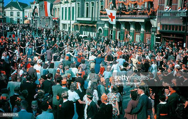 The townspeople of Eindhoven in the Netherlands dance in a circle during celebrations of their liberation from Nazi occupation 20th September 1944