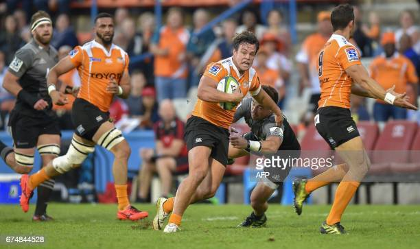 The Toyota Cheetahs' Nico Lee runs with the ball to escape a tackle by The Crusaders' David Havili during the SUPERXV rugby union match between The...