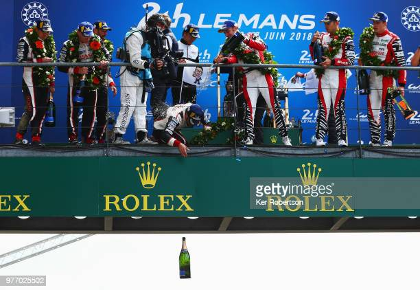 The Toyota Gazoo Racing TS050 Hybrid team driver Fernando Alonso drops a bottle of champagne to team mates as he and co drivers Kazuki Nakajima and...