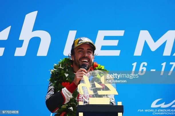 The Toyota Gazoo Racing TS050 Hybrid team driver Fernando Alonso reacts as he and co drivers Kazuki Nakajima and Sebastien Buemi celebrate after...