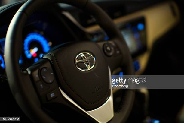 The Toyota Motor Corp. Logo is seen on the steering wheel of the new2018 Toyota Corolla vehicle as it sits on display during the company's launch...
