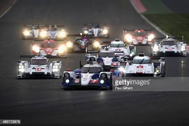 The Toyota Racing TS040 Hybrid LMP1 driven by Kazuki Nakajima of Japan, Stephane Sarrazin of France and Alexander Wurz of Austria leads the pack into...