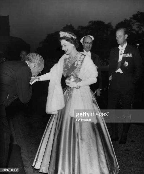 The traditional greeting of a kiss on the hand is acknowledged with a smile by Queen Elizabeth II as followed by the Duke of Edinburgh she arrives at...