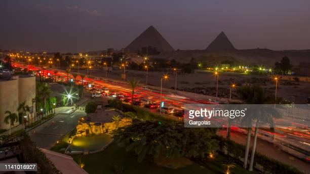 the traffic of the cairo and view on the pyramids at night - cairo stock pictures, royalty-free photos & images