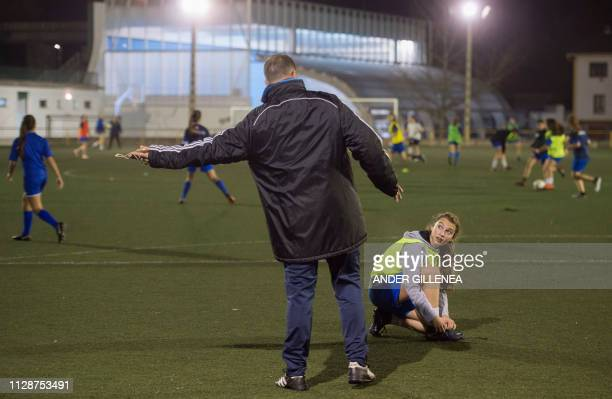The trainer speaks with a players of Anorga KKE football school during a training session in the Spanish Basque city of San Sebastian on February 18...