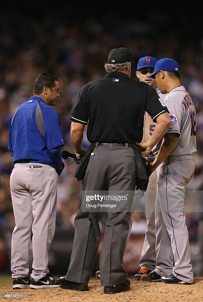 The trainer visits the mound to check on Daisuke Matsuzaka #16 of the New York Mets as he works against the Colorado Rockies at Coors Field on May 3, 2014 in Denver, Colorado. The Rockies defeated the Mets 11-10.