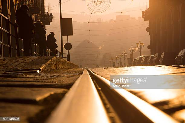 The tram line railways reflected with the beautiful orange sunrise light in the Turin city.