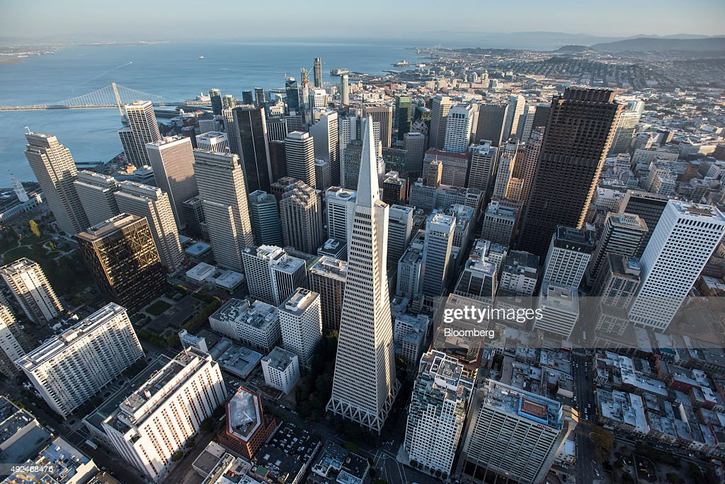 The Transamerica Pyramid building, center, stands in the skyline of downtown as the San Francisco-Oakland Bay Bridge is seen in this aerial photograph taken above San Francisco, California, U.S., on Monday, Oct. 5, 2015. With tech workers flooding San Francisco, one-bedroom apartment rents have climbed to $3,500 a month, more than in any other U.S. city. Photographer: David Paul Morris/Bloomberg via Getty Images