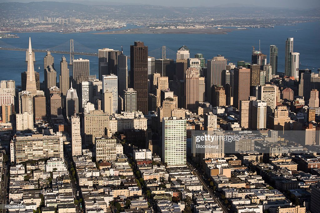The Transamerica Pyramid building, left, stands in the skyline of downtown as the San Francisco-Oakland Bay Bridge is seen in this aerial photograph taken above San Francisco, California, U.S., on Monday, Oct. 5, 2015. With tech workers flooding San Francisco, one-bedroom apartment rents have climbed to $3,500 a month, more than in any other U.S. city. Photographer: David Paul Morris/Bloomberg via Getty Images