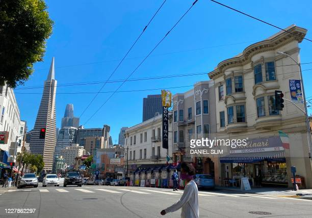 The Transamerica Pyramid is seen in the distance as people walk around in San Francisco, California, on July 31, 2020.