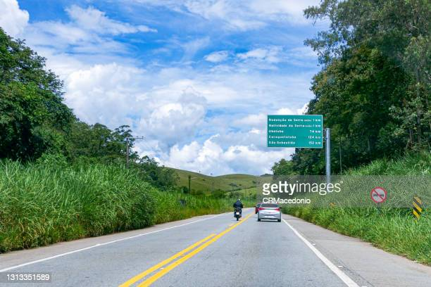 the transit on the oswaldo cruz highway in the middle of nature and under blue sky between clouds. - crmacedonio photos et images de collection