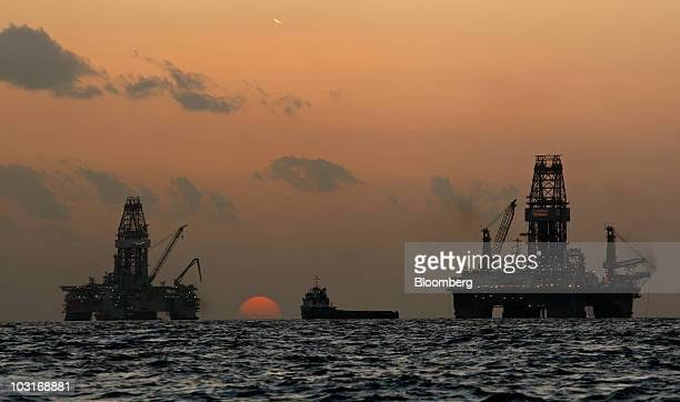 The Transocean Development Driller III and Transocean Development Driller II are silhouetted against the setting sun along with vessels leased by BP...