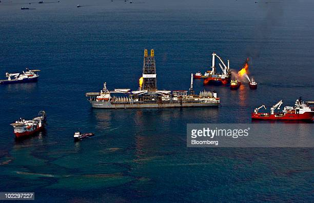 The Transocean Ltd Discoverer Enterprise drillship center burns off gas carried up with collected oil as the Transocean Q4000 platform right burns...