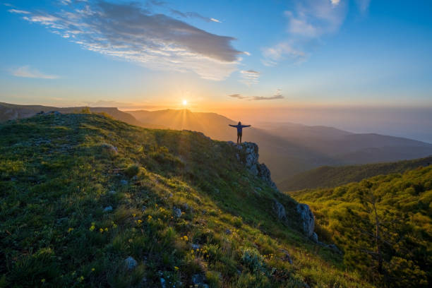 the traveler welcomes the sun at dawn in the highlands. summer landscape with the sun. in the distance you can see the sea. - free images without copyright stock pictures, royalty-free photos & images