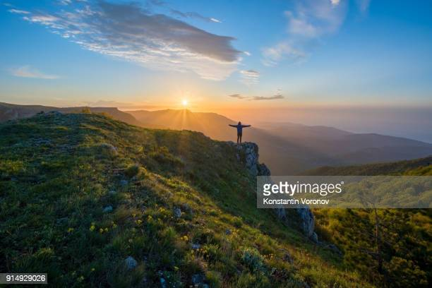 the traveler welcomes the sun at dawn in the highlands. summer landscape with the sun. in the distance you can see the sea. - religion stock pictures, royalty-free photos & images