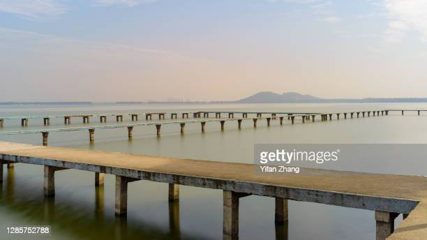 the trestle bridge in wuhan east lake at daytime - wuhan city stock pictures, royalty-free photos & images