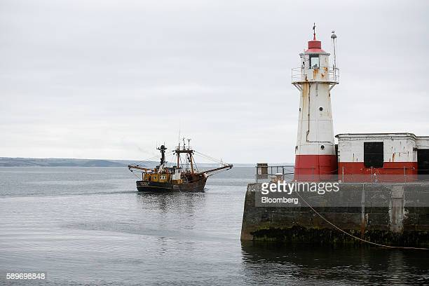 The Trevessa IV fishing trawler vessel passes a lighthouse as it heads out into the English channel after leaving Newlyn harbour in Newlyn UK on...
