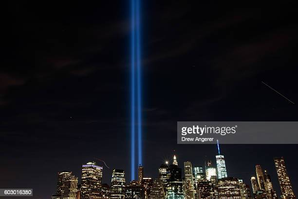 The Tribute in Light illumiinates the skyline of Lower Manhattan as seen from the Brooklyn Heights Promenade September 11 2016 in New York City...