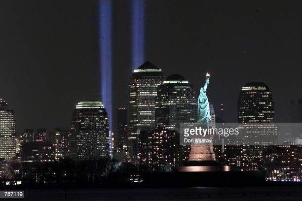 The Tribute in Light memorial shines behind the Statue of Liberty March 11 2002 on the sixmonth anniversary of the World Trade Center terrorist...