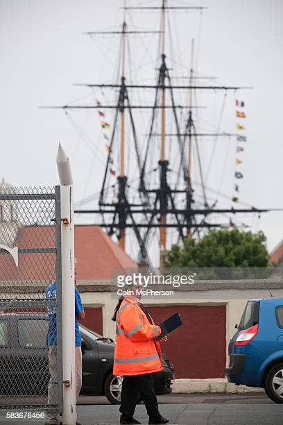 The Trincomalee an historic floating warship permanently moored in Hartlepool marina provides the backdrop as a steward regulates the car parking at...