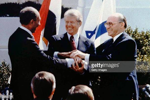 The triple handshake between Egyptian President Anwar Sadat US President Jimmy Carter and Israeli Prime Minister Menahem Begin seals the signing of...